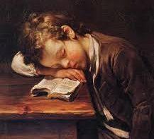 Jovem estudante a dormir sobre o seu livro